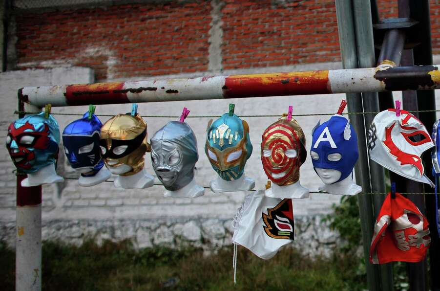 Mexican Lucha Libre wrestling masks are attached with clothespins to a wire, on display for sale in