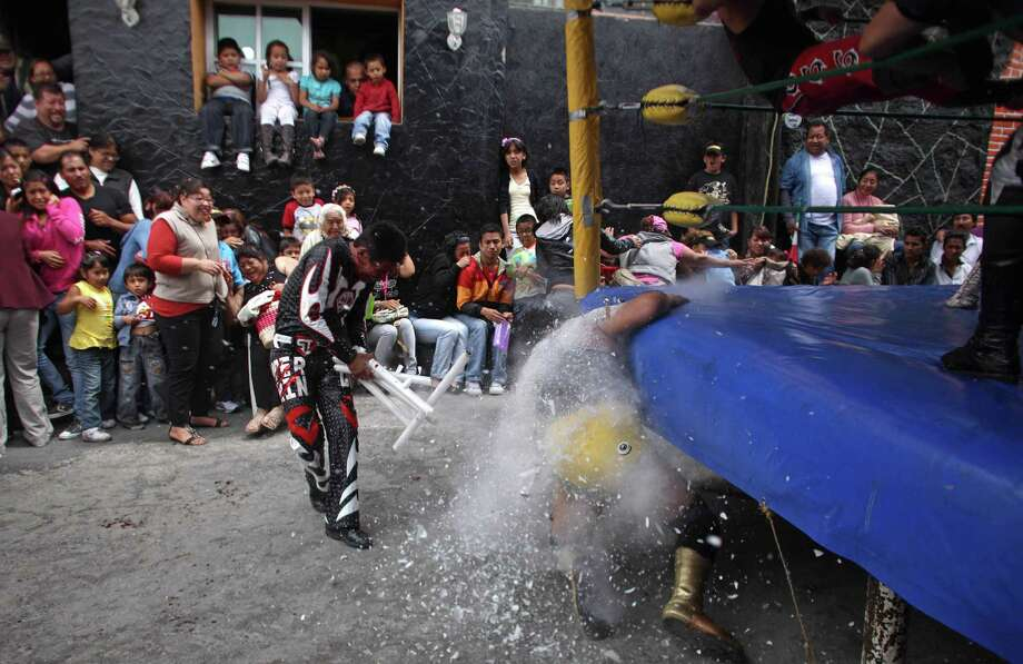 Mexican Lucha Libre wrestlers Super Tarin breaks lamps on the back of Leon Dorado during a performance in a poor neighborhood at the outskirts of Mexico City. Photo: Alexandre Meneghini, Associated Press / AP