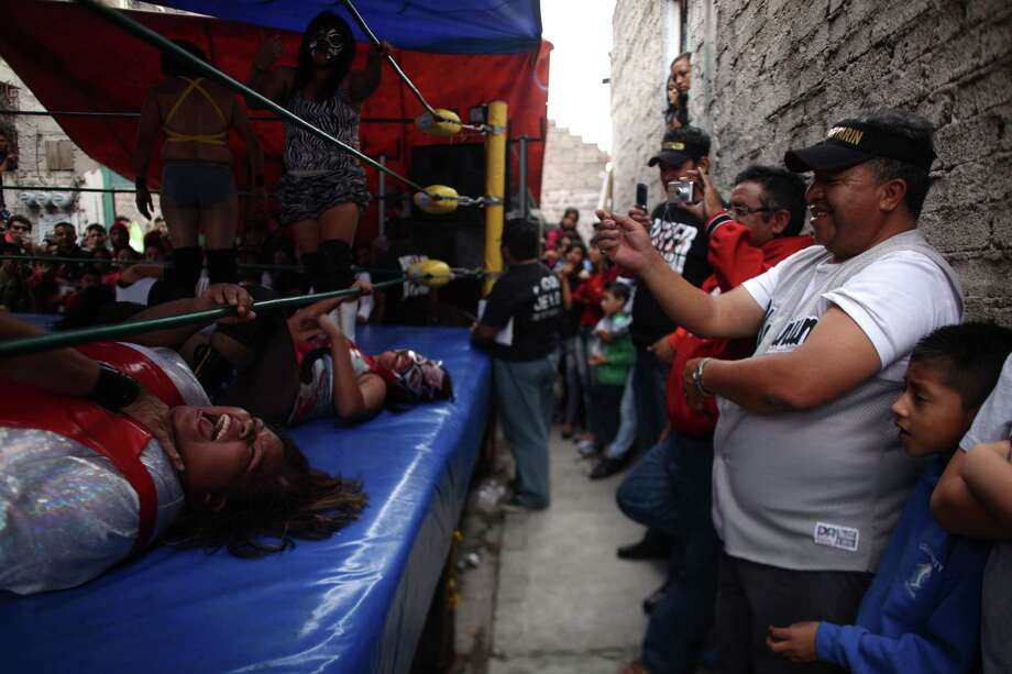 Fans watch as watch Mexican Lucha Libre wrestlers Big Mama, left, and Black Fury, are overtaken by their opponents during a performance in a Caravan Super Tarin traveling wrestling show. Photo: Alexandre Meneghini, Associated Press / AP