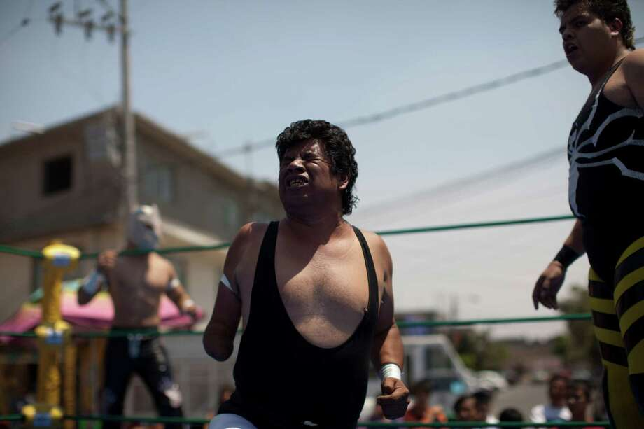 Mexican Lucha Libre wrestler Desafio, center, grimaces during his performance in a Caravan Super Tarin. Photo: Alexandre Meneghini, Associated Press / AP