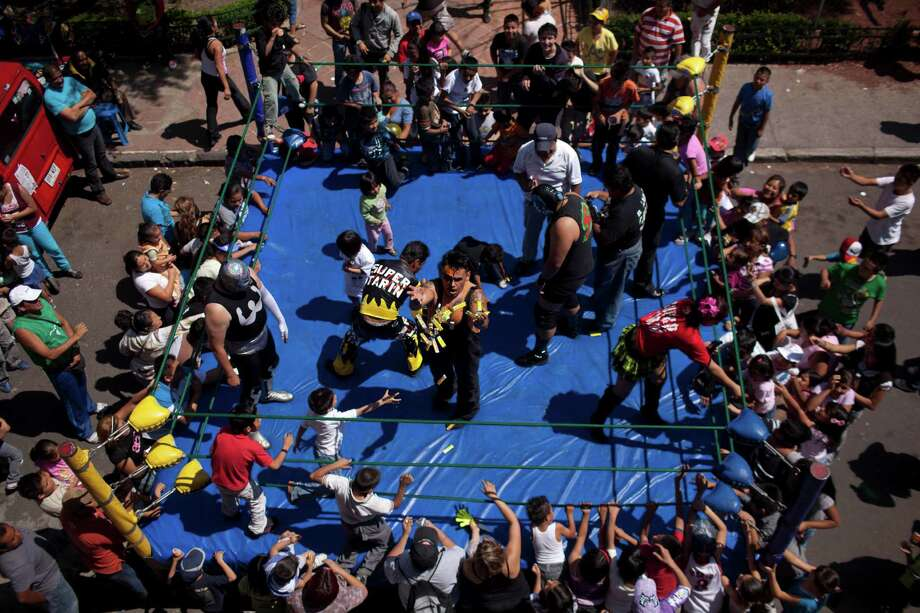 Mexican Lucha Libre wrestler Halloween, center, tosses sweets to children prior to his performance in a poor neighborhood in downtown Mexico City. Photo: Alexandre Meneghini, Associated Press / AP