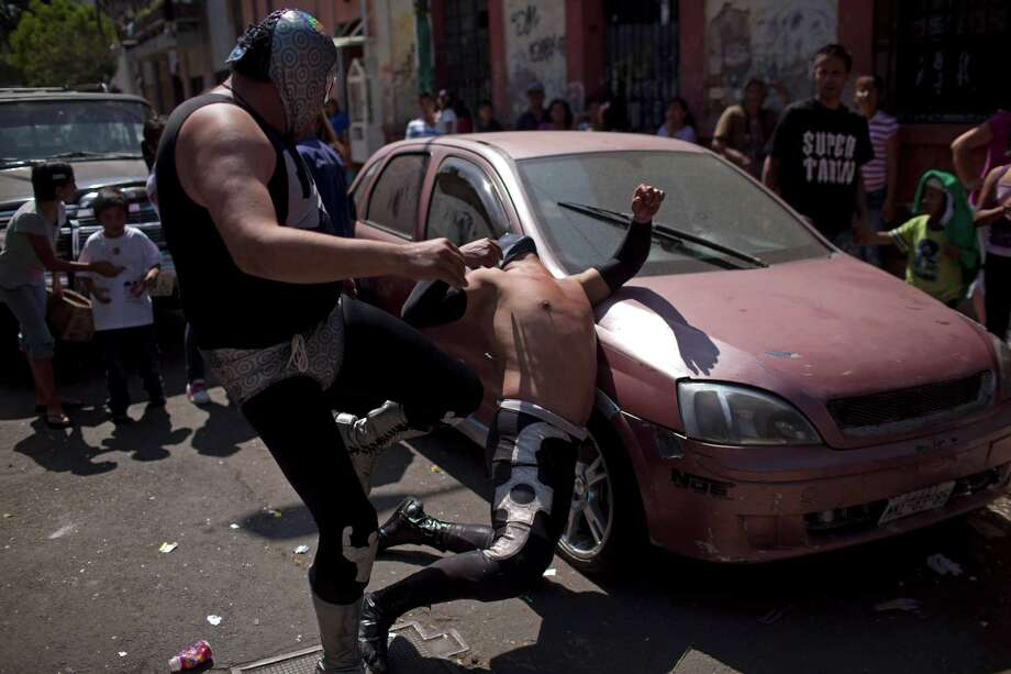 Mexican Lucha Libre wrestlers Brazo de Plata Junior, left, and Shadow perform outside the ring in a poor downtown neighborhood in Mexico City. Photo: Alexandre Meneghini, Associated Press / AP