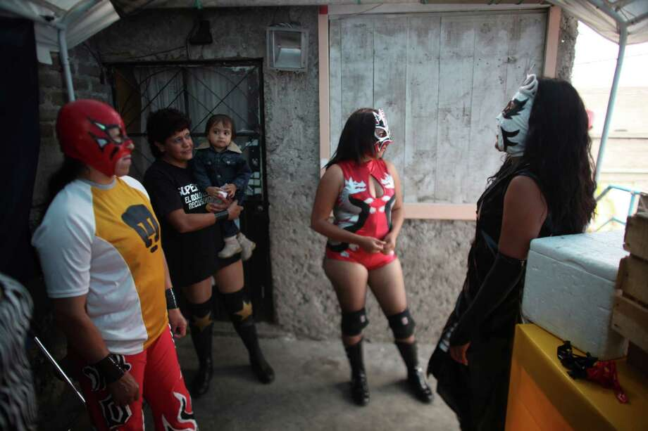 Mexican Lucha Libre wrestlers Dama del Ring, right, Black Fury, second right, Estrella de Fuego, second left and La Chola, wait for their turn to perform in a Caravan Super Tarin traveling wrestling show on the outskirts of Mexico City. Photo: Alexandre Meneghini, Associated Press / AP