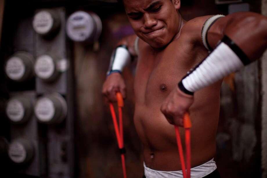 Mexican Lucha Libre wrestler Nino de Ebano warms up before his performance. Photo: Alexandre Meneghini, Associated Press / AP