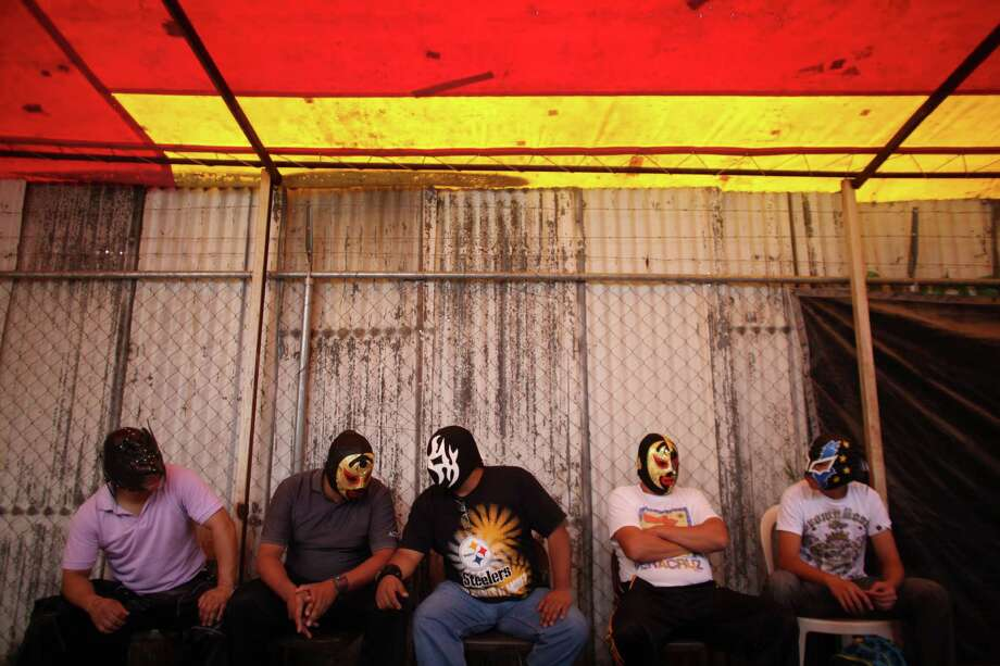 Mexican Lucha Libre wrestler Chicago Rouge, center, visits with another wrestler prior to their performance on a grassy lot in a makeshift wrestling ring in Coacalco, Mexico. Photo: Alexandre Meneghini, Associated Press / AP