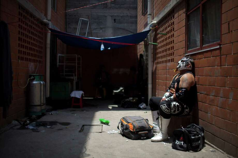 Mexican Lucha Libre wrestler Lunathor rests after his performance in a poor downtown neighborhood in Mexico City. Photo: Alexandre Meneghini, Associated Press / AP