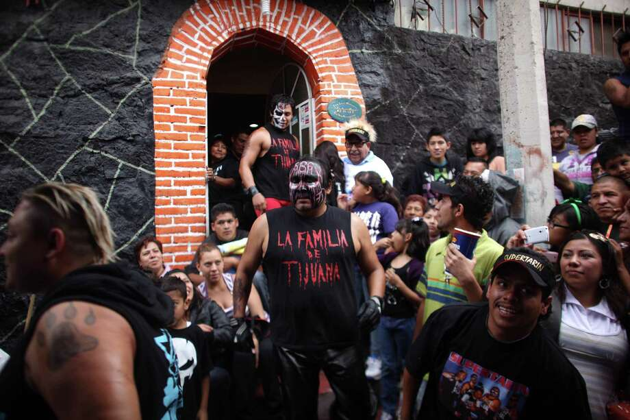 Lucha Libre wrestlers Damian 666, center, and his son Bestia 666,  walk towards the ring to perform. Photo: Alexandre Meneghini, Associated Press / AP