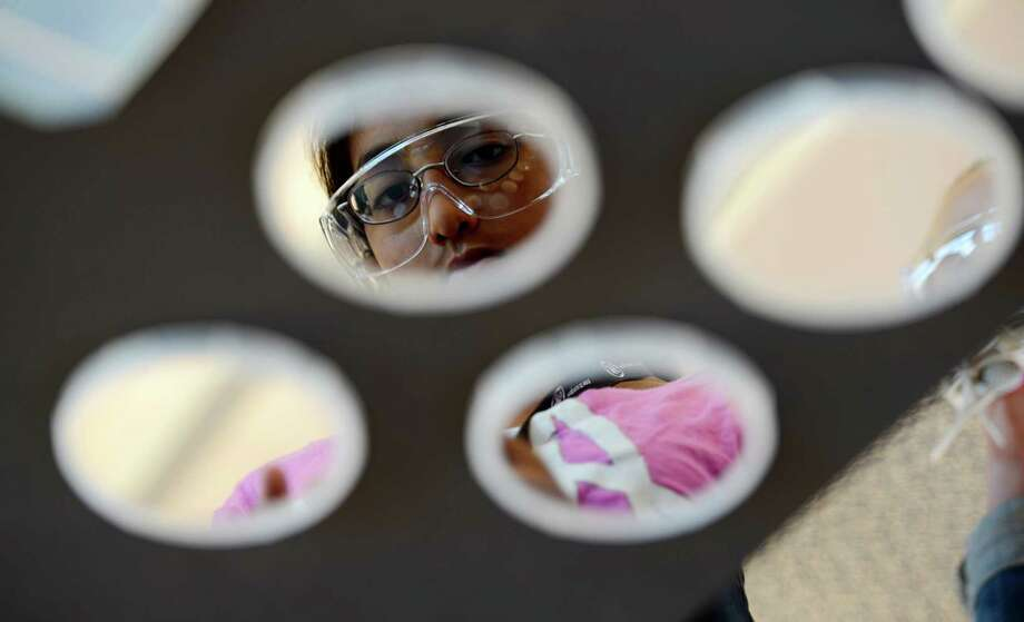 Aspiring scientist Meghna Tatembe from Niskyauna School District's Engineering Institute for Young Women is reflected in reflective medium during a discussion of solar technology at the GE Global Research in Niskayuna, N.Y. July 9, 2012.      (Skip Dickstein/Times Union) Photo: Skip Dickstein / 00018388A