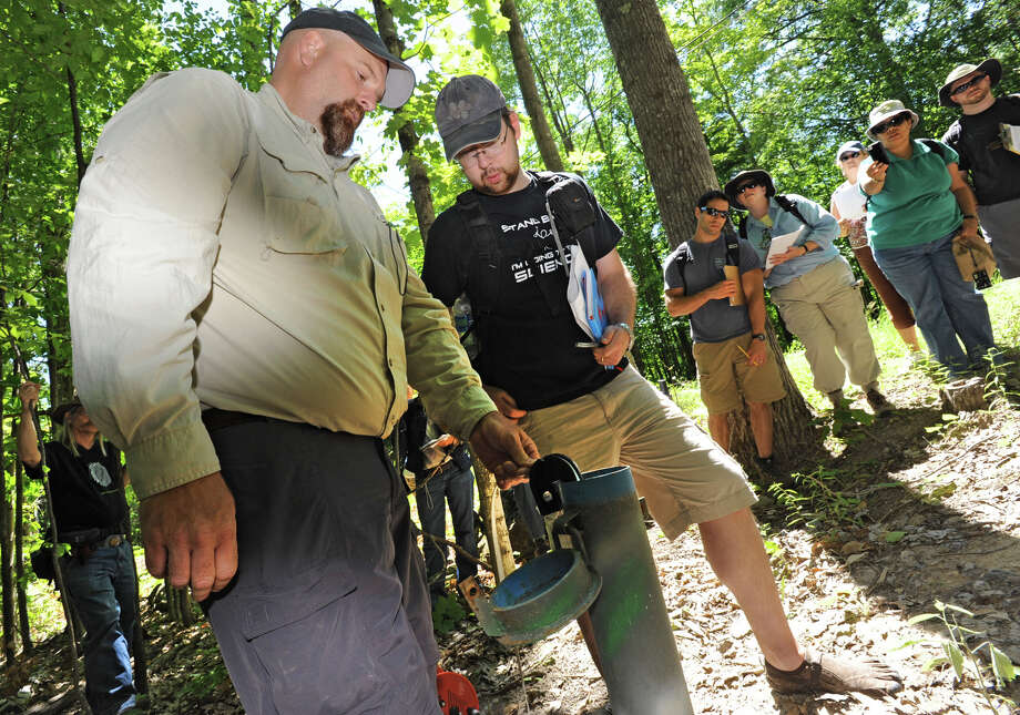 From left, Brian Bird Ph,D., Glacial Geologist with NYSGS, shows Sean Ellison, a teacher at Norwood-Norfork Central School, how to measure water in a monitoring well using a pressure transducer Monday, July 9, 2012 in Keene Valley, N.Y. New York State Museum Geologist Dr. Andrew Kozlowski and Brian Bird lead 26 Earth Science teachers from across New York State on a tour of the 82-acre Keene Valley landslide as part of a lesson on geologic hazards and glacial deposits in the state. (Lori Van Buren / Times Union) Photo: Lori Van Buren