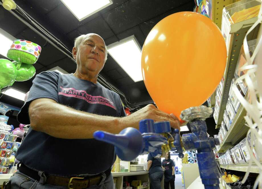 Jerry Sykes, of the Party Warehouse in Colonie, N.Y. July 6, 2012 fills a helium ballon.   (Skip Dickstein/Times Union) Photo: Skip Dickstein / 00018376A