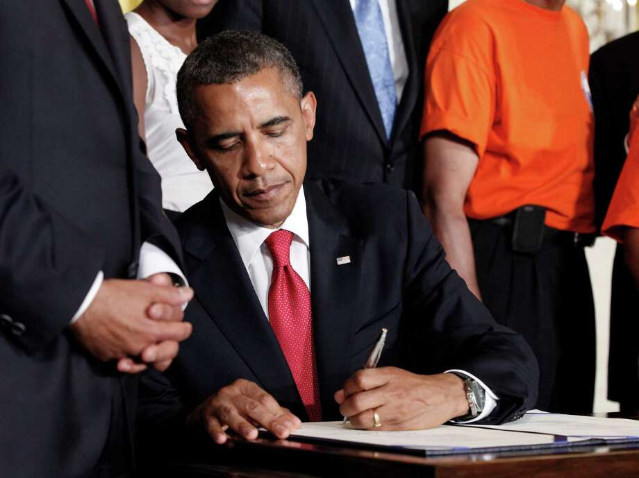 FILE - In this July 6, 2012 file photo, President Barack Obama signs the Surface Transportation Bill, in the East Room of the White House in Washington.  A new law reduces by billions of dollars what companies have to contribute to their pension funds, raising concerns about weakening the plans that millions of Americans count on for retirement.  But with many companies already freezing or getting rid of pension plans, critics are reluctant to force the issue or even make much of a fuss.  (AP Photo/Pablo Martinez Monsivais, File) Photo: Pablo Martinez Monsivais