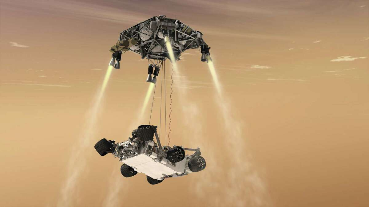"""This artist's rendering provided by NASA/JPL-Caltech shows a """"sky crane"""" lowering the rover Curiosity onto Mars' surface."""