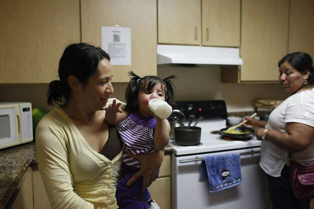 Socorro Quezada (l to r) holds her daughter Deilayana Quezada, 16 months, as she enjoys a bottle in a shared dining area at the First Step for Families on Monday, July 9, 2012 in San Mateo, Calif.  First Step for Families is run by Inn Vision Shelter Network. Photo: Lea Suzuki, The Chronicle