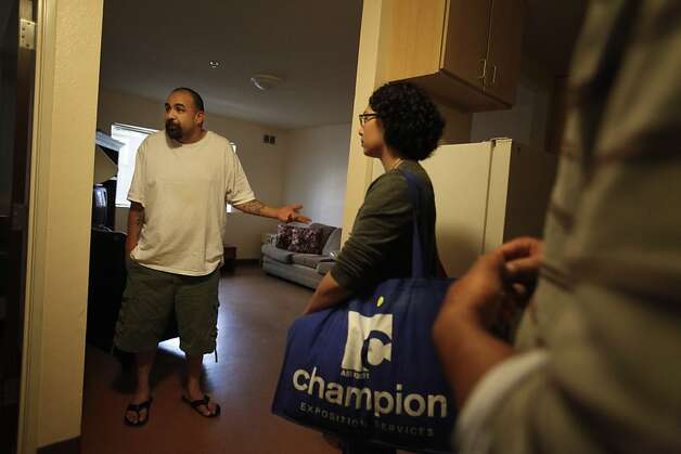 Conrad Rivera (left) stands in his transitional apartment at the First Step for Families as Maria Duzon (center) communications manager Inn Vision Network Shelter, listens to him talk on Monday, July 9, 2012 in San Mateo, Calif.  First Step for Families is run by Inn Vision Shelter Network. Photo: Lea Suzuki, The Chronicle