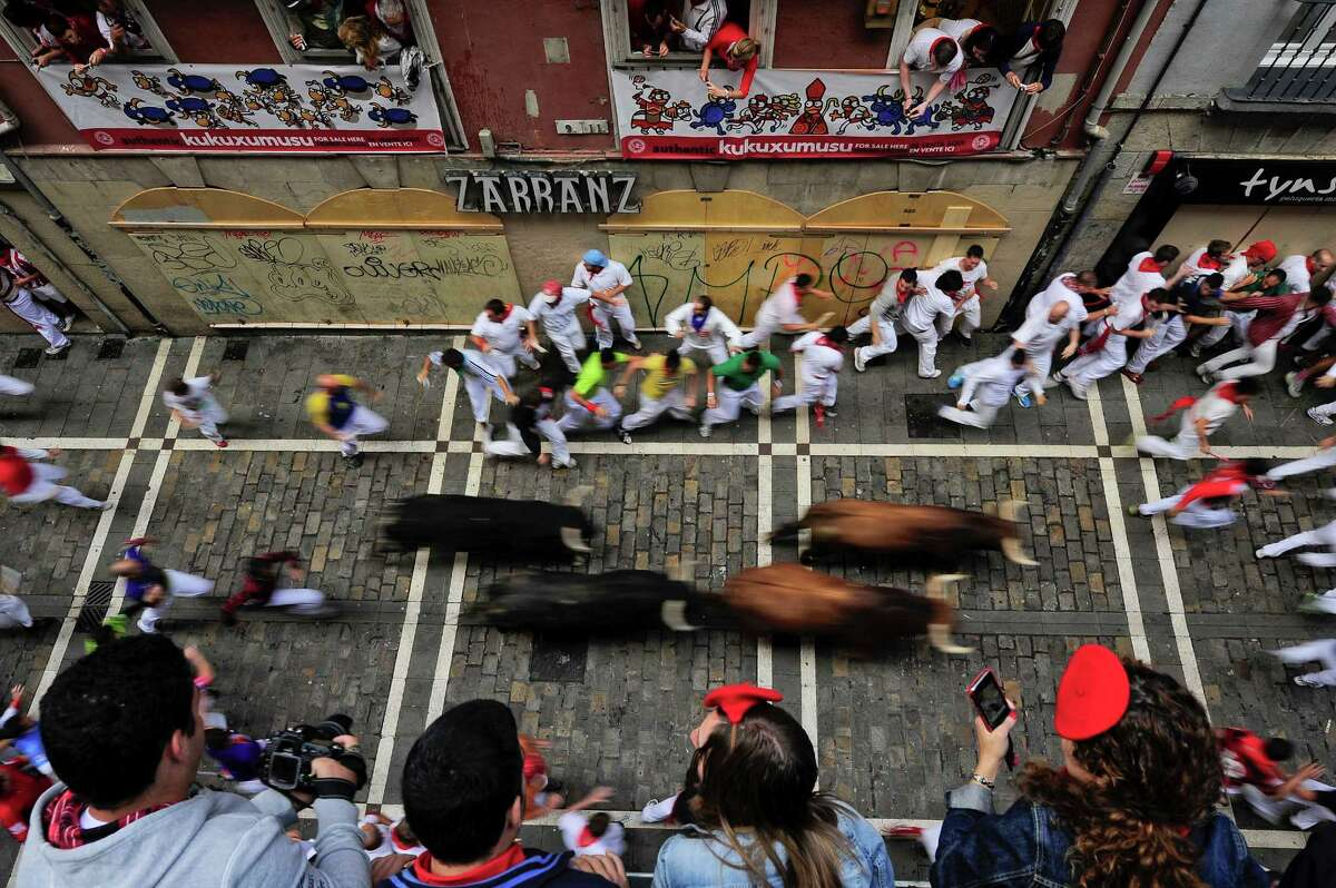 People look on from balconies as revelers run on Estafeta street beside to El Pilar fighting bulls ranch, during the fourth running of the bulls at the San Fermin fiestas, in Pamplona northern Spain, Tuesday, July 10, 2012.