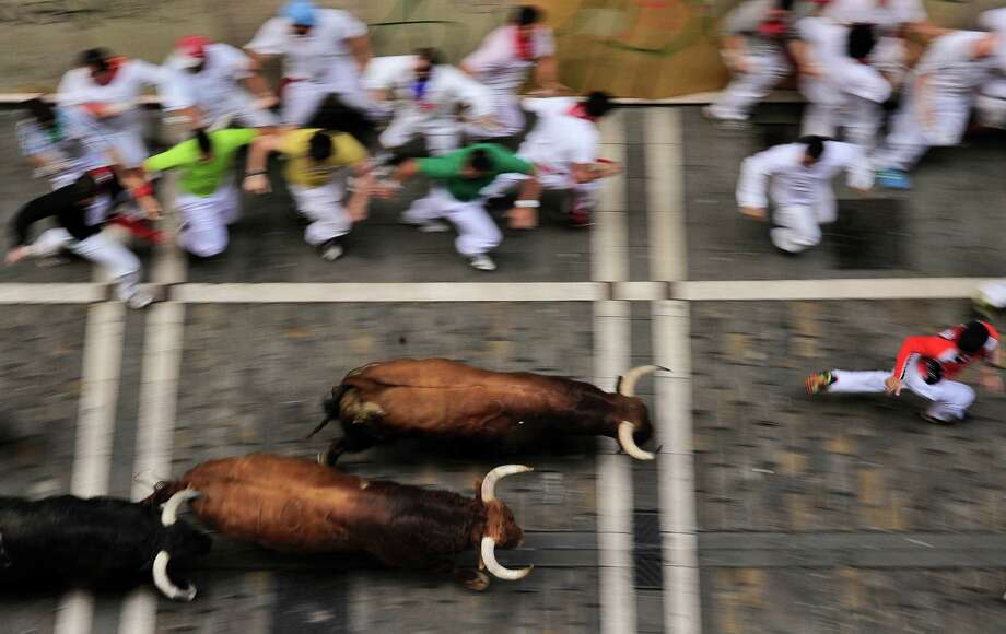 Revelers run on Estafeta street beside to El Pilar fighting bulls ranch, during the fourth running of the bulls at the San Fermin fiestas, in Pamplona northern Spain, Tuesday, July 10, 2012. Photo: Alvaro Barrientos