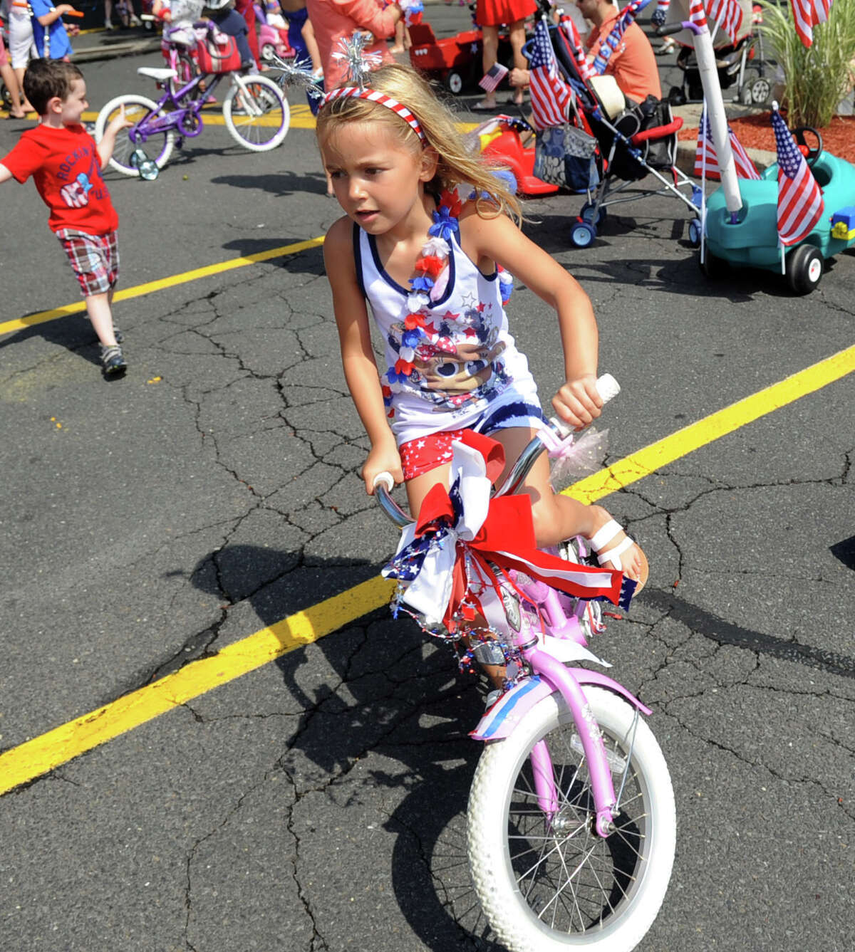 Caitlyn Lodge, 6, rides her bike during Wednesday's YWCA Push-n-Pull Parade in Darien on July 4, 2012.