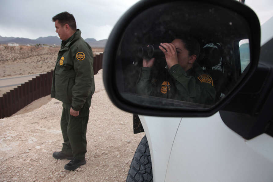 Border Patrol Agent Jacob Nunez overlooks the valley with another border patrol agent who uses binoc