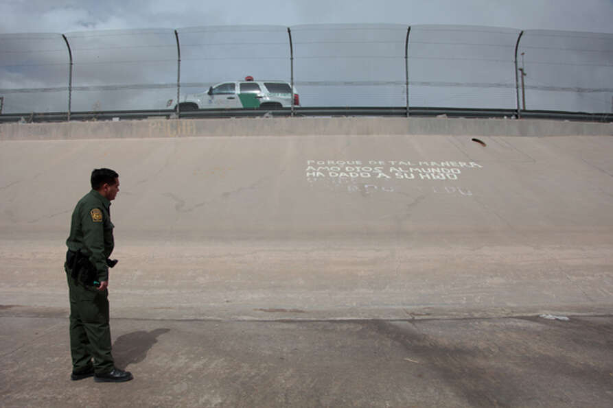 Border Patrol Agent John Urquidi reads graffiti written by Mexican Nationals along the banks of the
