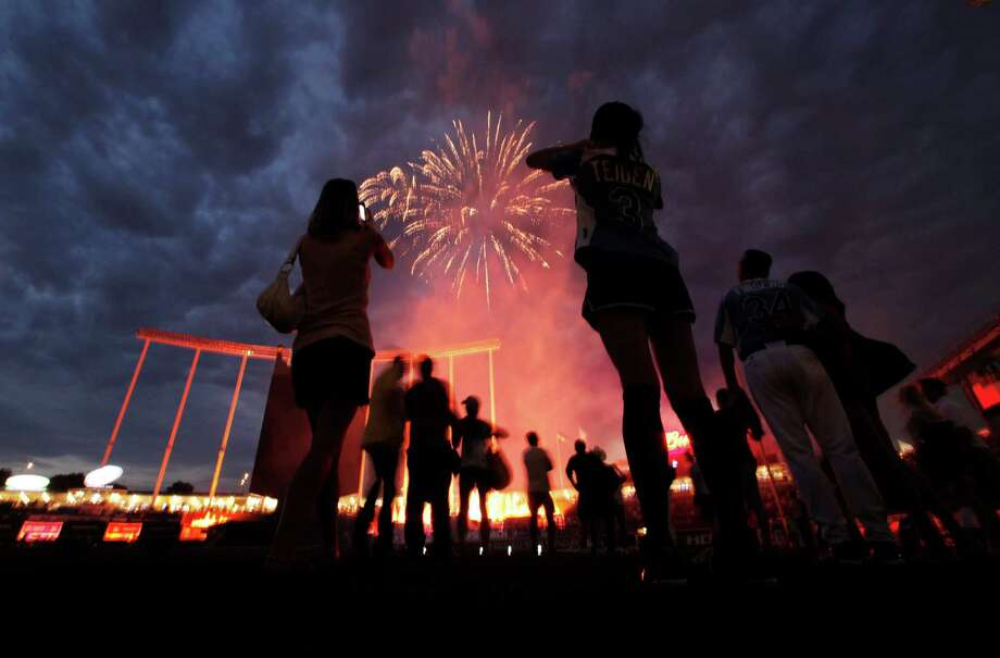 Players watch the fireworks after the MLB All-Star celebrity softball game, Sunday, July 8, 2012, in Kansas City, Mo. Photo: Charlie Riedel, AP / AP