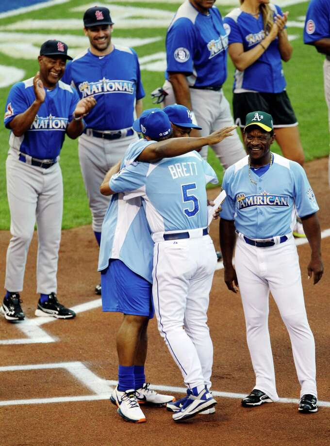 Hall of Famer George Brett (5) and former baseball and football star Bo Jackson hug as Hall of Famer Ozzie Smith, left, actor Jon Hamm, and Hall of Famer Rickey Henderson watch during player introductions for the MLB All-Star celebrity softball game, Sunday, July 8, 2012, in Kansas City, Mo. Photo: Charlie Neibergall, AP / AP