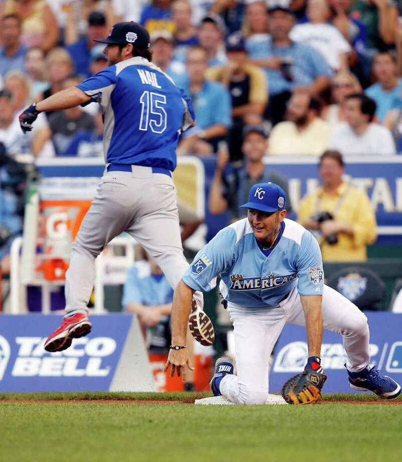 KANSAS CITY, MO - JULY 08:  David Nail leaps over former player Mike Sweeney while attempting to reach first base during the Taco Bell All-Star Legends & Celebrity Softball Game at Kauffman Stadium on July 8, 2012 in Kansas City, Missouri. Photo: Jamie Squire, Getty Images / 2012 Getty Images