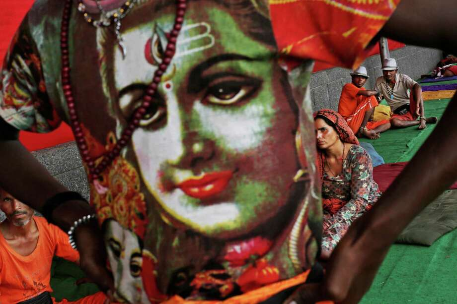 A Kanwarias, or worshipper of Hindu God Shiva, wears a t-shirt showing Lord Shiva as he and others rest during a pilgrimage carrying water from the River Ganges in New Delhi, India, Tuesday, July 10, 2012. Kanwarias are devotees performing a ritual pilgrimage in which they walk the roads of India, clad in saffron, and carrying ornately decorated canisters of the sacred water of the Ganges River over their shoulders, to take it back to Hindu temples in their hometowns, during the Hindu lunar month of Shravana. Photo: Kevin Frayer, AP / AP