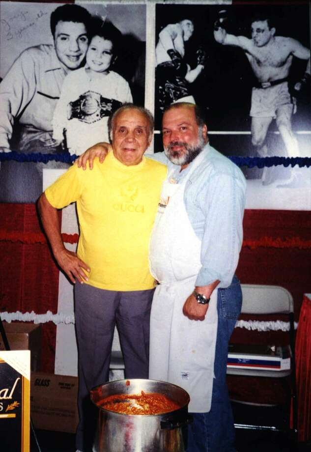 Joe LaMotta, right, president of LaMotta Foods Inc., stands with his father, former middleweight boxing champion Jake LaMotta, in the booth promoting their LaMotta Tomatta Sauce at the International Fancy Foods show in New York's Jacob Javitts Center in June 1998. Photo: AP