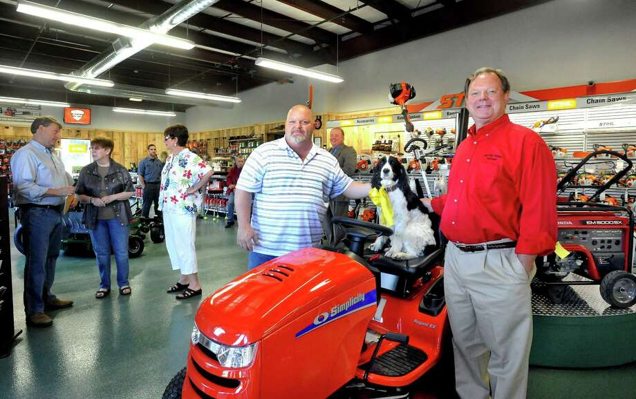 Business partners Kevin Dee, center, and Mark Guss, right, stand with Molly, sitting on a Simplicity tractor, at the opening of Bethel Power Equipment at their new location Tuesday, July 10, 2012. Photo: Michael Duffy / The News-Times