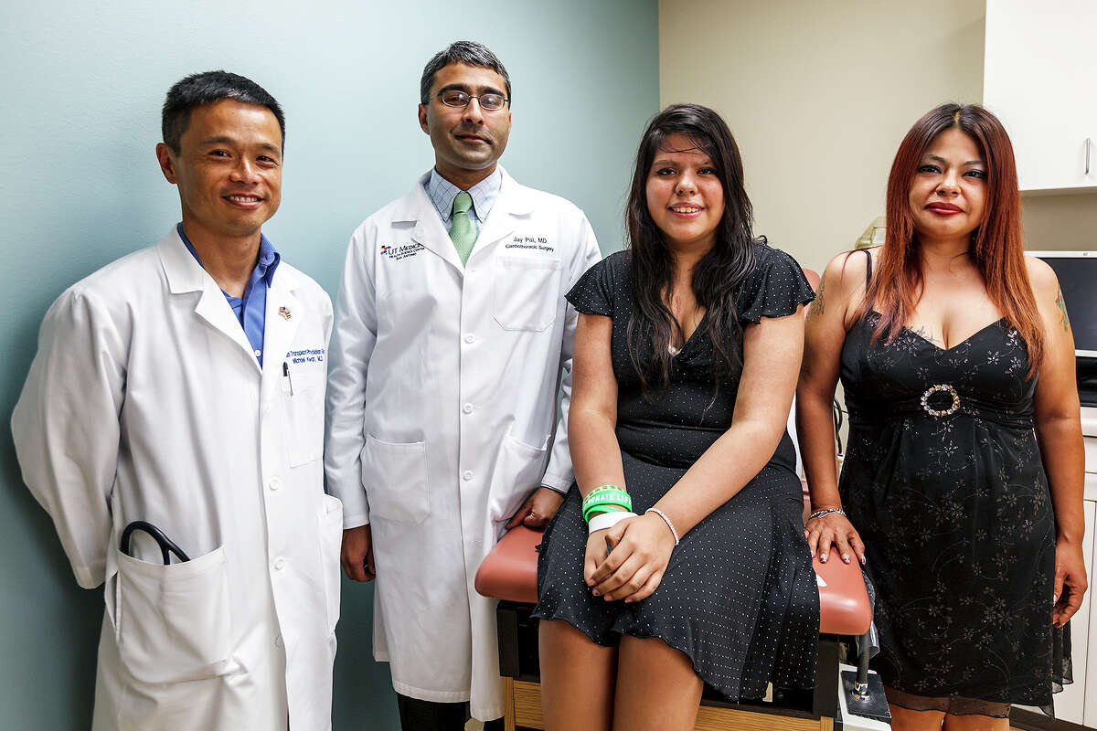 Amber Munoz (second from right) poses with her mother, Valerie Munoz, Michael Kwan, M.D.,FACC, Medical Director, Texas Transplant Institute Heart Failure and Transplant Program (left) and Jay Pal, M.D., Ph.D. of UT Medicine San Antonioat the Methodist Heart Hospital Heart Failure and Heart Transplant Clinic, 4499 Floyd Curl, on July 3, 2012. Amber, a 15-year-old student at Taft High School, received a heart transplant at the Methodist Heart Holpital on April 4 to replace her enlarged one. She had earlier received aleft-ventricular assist device (LVAD) that enabled her to stay alive for 48 days while surgeons and her family awaited the donor heart, which came from a young organ donor. Amber is one of the youngest patients in the world to be bridged to transplant in this manner. Photo by Marvin Pfeiffer / Prime Time Newspapers