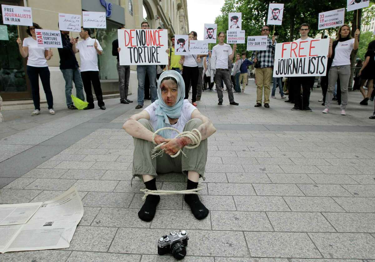 Reporters Without Borders activists, bound and made up as mock victims, demonstrate outside the Iran Air office on the Champs Elysées in Paris, France, on Tuesday to protest against the imprisonment of Iranian journalists.