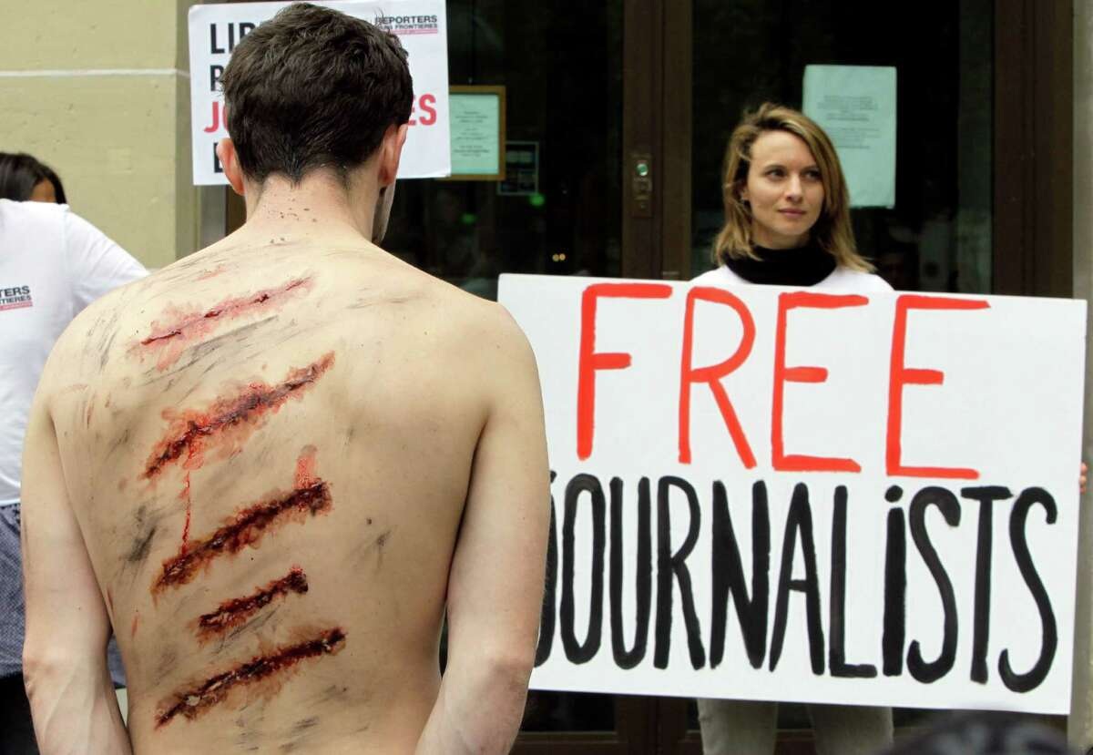 Reporters Without Borders activists, with mock injuries, demonstrate outside the Iran Air office on the Champs Elysées in Paris, France, on Tuesday to protest against the imprisonment of Iranian journalists.