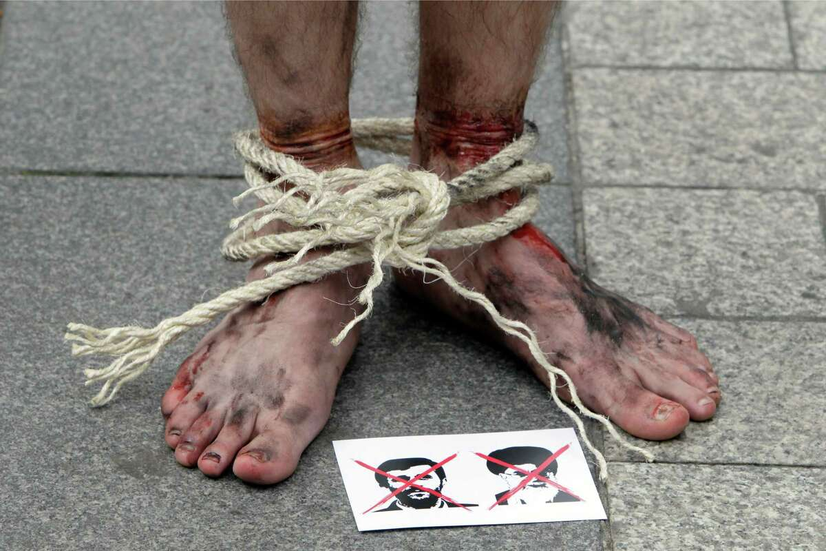 A leaflet representing Iranian President Mahmoud Ahmadinejad is seen as Reporters Without Borders activist, bound and made up as mock victims, demonstrate outside the Iran Air office on the Champs Elysées in Paris, France, on Tuesday to protest against the imprisonment of Iranian journalists.