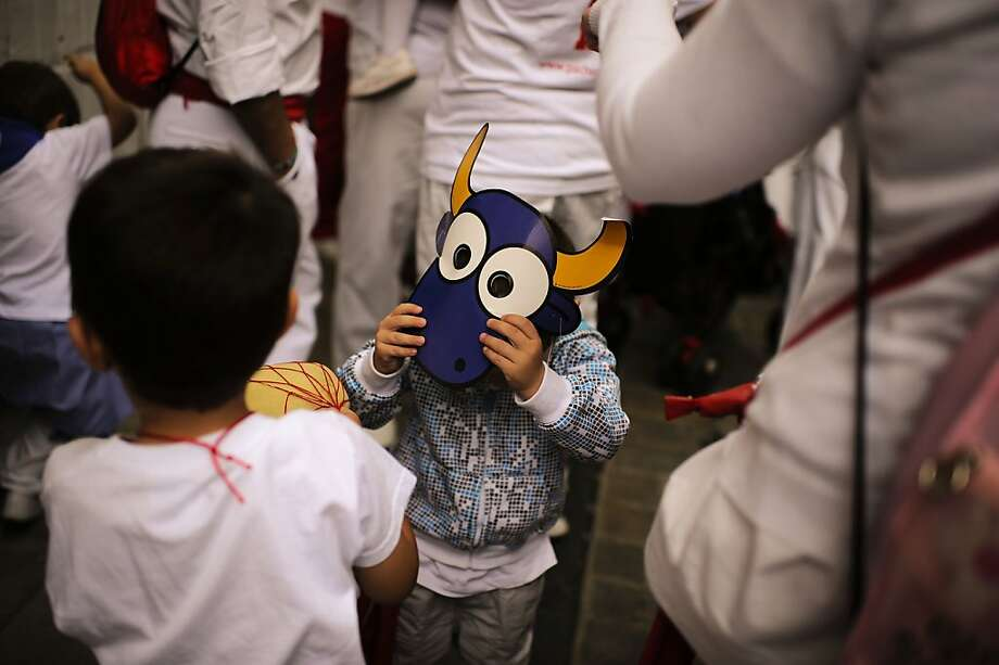 A young boy wears a mask of a bull at the San Fermin fiesta, in Pamplona northern Spain, Tuesday, July 10, 2012. (AP Photo/Alvaro Barrientos) Photo: Alvaro Barrientos, Associated Press