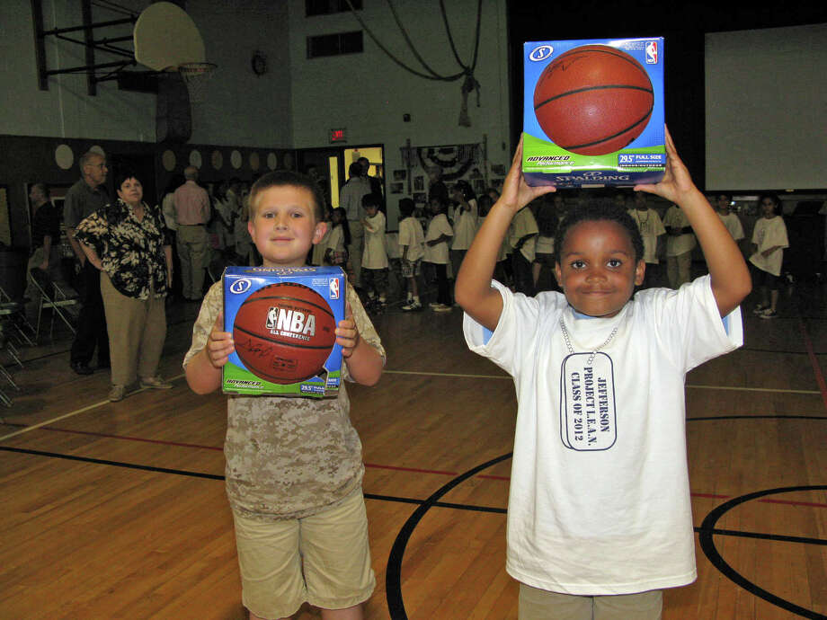 Aidan Carroll, left, and Terrence Kit, receive basketballs signed by Miami Heat forward Chris Bosh for their outstanding performance in the Project L.E.A.N. program. Photo: Contributed Photo
