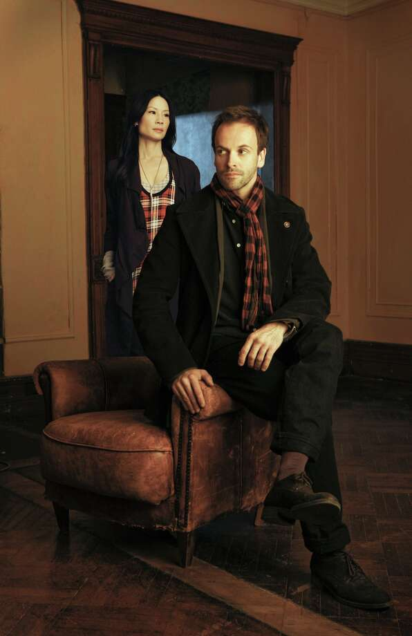"In ""Elementary,"" Sherlock Holmes (Jonny Lee Miller) solves crimes with Dr. Watson (Lucy Liu).  Photo: CBS"