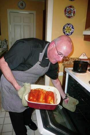 "Father Matt removes his freshly cooked manicotti, topped with a homemade basil tomato sauce, from the oven.  ""You can always tell it's done when the sauce starts to bubble on the sides of the baking dish,"" he says/ Photo: Anne W. Semmes"