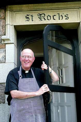 The Rev. Matthew Mariello, priest and cookbook author, poses in front of the rectory St. Roch Church, where he prepares his favorite Italian dishes. Photo: Anne W. Semmes