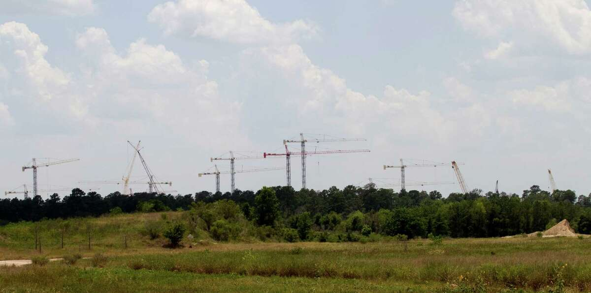 Construction cranes rise above the trees at the site of the Exxon Mobil Corp. campus near The Woodlands. The 385-acre tract is being developed, near I-45 and the Hardy Toll Road, as the energy corporation's new corporate campus. The development will include multiple low-rise office buildings; lab, conference and training centers; a child care facility; and a wellness center.