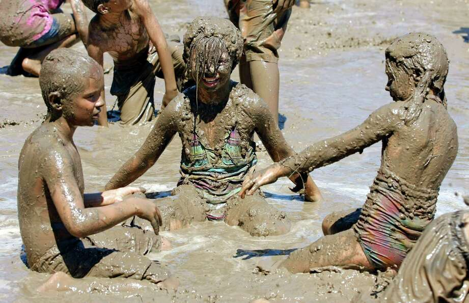 Kids play in a giant lake of mud at the 25th annual