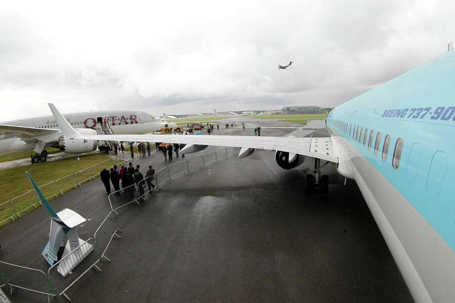 Visitors shelter from the rain underneath a wing of a Boeing 737-900ER on display at the Farnborough International Airshow, Farnborough, England, Tuesday, July 10, 2012. On the left on display is a Boeing 787 Dreamliner. (AP Photo/Sang Tan) Photo: Sang Tan, Associated Press / AP