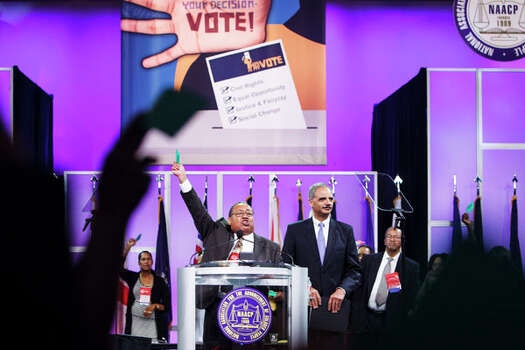 Leon Russell, left, holds up a voting card as he asks voters to adopt the resolution backing Attorney General Eric Holder. Photo: Michael Paulsen, . / © 2012 Houston Chronicle