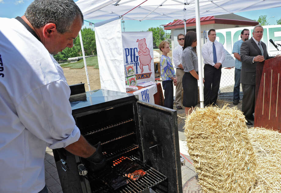 Troy Mayor Lou Rosamilia announces Troy Pig Out Tuesday, July 10, 2012 in Troy, N.Y. He also announced it's time for updates on the rebuilding of Riverfront Park, most of which will reopen this weekend. At left, Kevin Rundell, pit master for the Purple Pork Masters, prepares pork spare ribs on the smoker. (Lori Van Buren / Times Union) Photo: Lori Van Buren