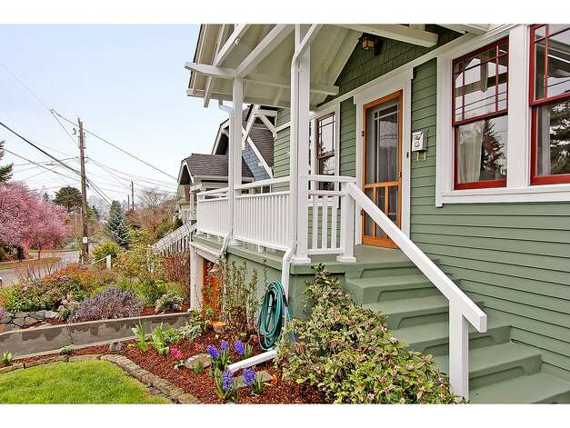 Front porch of 3929 Ashworth Ave. N. The 2,585-square-foot Craftsman, built in 1924, has five bedrooms and 2.5 bathrooms -- including a lower level with two bedrooms, a media room, a five-piece bathroom and a kitchenette -- built-in shelves and a back deck on a 3,579-square-foot lot. It's listed for $665,000. Photo: Courtesy Richae Fox And Carolyn Holm/Windermere Real Estate