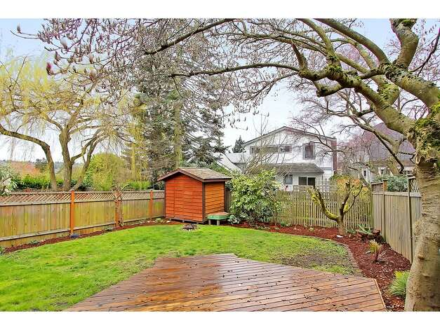 Back deck and yard of 3929 Ashworth Ave. N. The 2,585-square-foot Craftsman, built in 1924, has five bedrooms and 2.5 bathrooms -- including a lower level with two bedrooms, a media room, a five-piece bathroom and a kitchenette -- built-in shelves, a balcony and a front porch on a 3,579-square-foot lot. It's listed for $665,000. Photo: Courtesy Richae Fox And Carolyn Holm/Windermere Real Estate