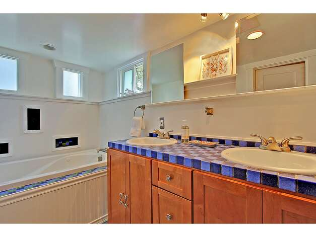 Lower-level five-piece bathroom of 3929 Ashworth Ave. N.. The 2,585-square-foot Craftsman, built in 1924, has five bedrooms and 2.5 bathrooms, built-in shelves, a balcony, a front porch and a back deck on a 3,579-square-foot lot. It's listed for $665,000. Photo: Courtesy Richae Fox And Carolyn Holm/Windermere Real Estate