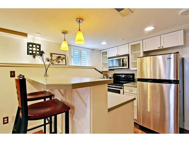 Lower-level kitchenette of 3929 Ashworth Ave. N. The 2,585-square-foot Craftsman, built in 1924, has five bedrooms and 2.5 bathrooms, built-in shelves, a balcony, a front porch and a back deck on a 3,579-square-foot lot. It's listed for $665,000. Photo: Courtesy Richae Fox And Carolyn Holm/Windermere Real Estate