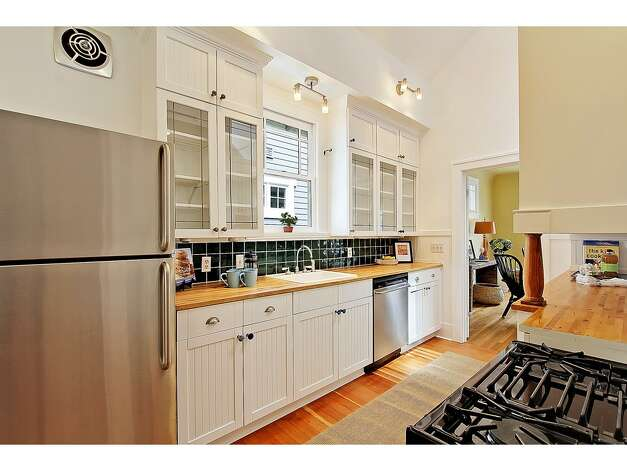 Kitchen of 3929 Ashworth Ave. N. The 2,585-square-foot Craftsman, built in 1924, has five bedrooms and 2.5 bathrooms -- including a lower level with two bedrooms, a media room, a five-piece bathroom and a kitchenette -- built-in shelves, a balcony, a front porch and a back deck on a 3,579-square-foot lot. It's listed for $665,000. Photo: Courtesy Richae Fox And Carolyn Holm/Windermere Real Estate