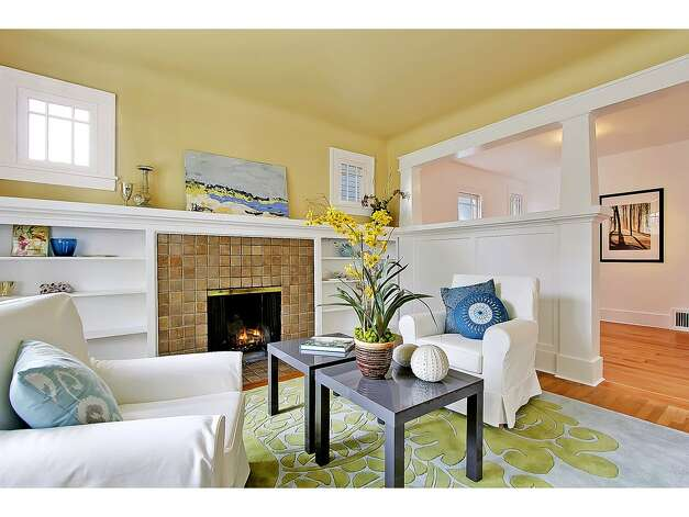 Living room of 3929 Ashworth Ave. N. The 2,585-square-foot Craftsman, built in 1924, has five bedrooms and 2.5 bathrooms -- including a lower level with two bedrooms, a media room, a five-piece bathroom and a kitchenette -- built-in shelves, a balcony, a front porch and a back deck on a 3,579-square-foot lot. It's listed for $665,000. Photo: Courtesy Richae Fox And Carolyn Holm/Windermere Real Estate