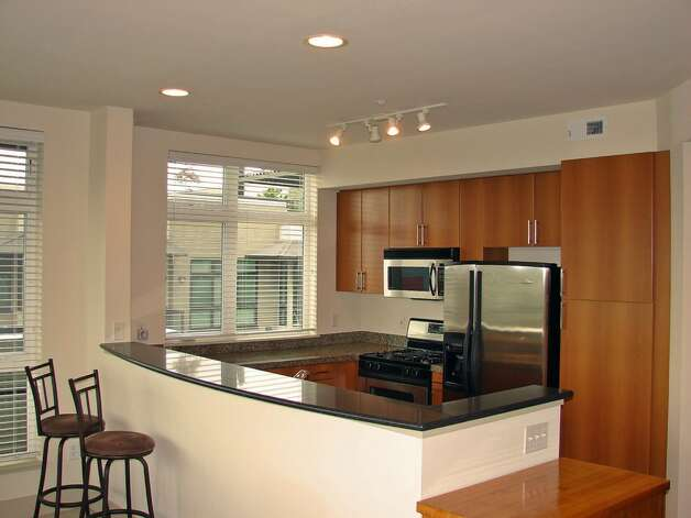 Kitchen of 1730 N. Northlake Way, Unit 311. The 1,069-square-foot home, built in 2002, has two bedrooms, two bathrooms, a gas fireplace, picture windows and a wrap-around deck with views of Lake Union and downtown. It's listed for $638,000. Photo: Mark Anderson/John L. Scott Real Estate